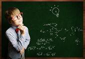 Smart boy in red glasses near blackboard with formulas
