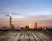 Taipei city night with famous landmark, 101 skyscraper, under blue and dramatic colorful sky in Taiwan, Asia. Focus on wooden floor.