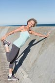 Active senior woman stretching on the pier on a sunny day