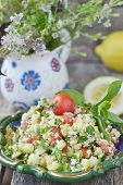 foto of tabouleh  - vegetables salad in to ornamental plate on wooden table [[** Note: Shallow depth of field ** Note: Visible grain at 100%, best at smaller sizes - JPG