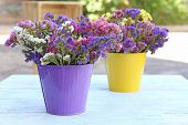 Beautiful flowers in flowerpot on wooden table, outdoors
