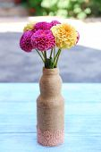 Dahlia flowers in vase on table, outdoors