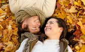 love, relationship, season, family and people concept - close up of smiling couple lying in autumn p