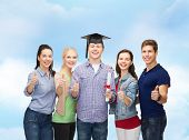 education and people concept - group of standing smiling students with diploma and corner-cap showin