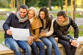 travel, vacation, people, tourism and friendship concept - group of smiling friends sitting with tab