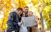 travel, vacation, people, tourism and friendship concept - group of smiling friends looking to map i