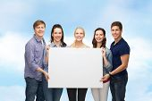 education and people concept - group of standing smiling students with white blank board