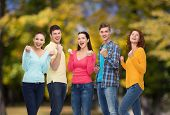 friendship, summer vacation, teamwork, gesture and people concept - group of smiling teenagers showi