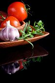 Tomatoes and garlic in wooden plate on black background.