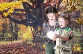 Two sisters amazed by a brilliant light sphere they found in the autumn woods.