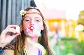 Hippie girl blow bubbles outdoors in village.