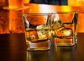 Whiskey On Bar Table With Ice On Warm Atmosphere