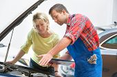pic of auto repair shop  - Auto mechanic and female customer in auto repair shop - JPG