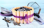Tasty cake Charlotte with blueberries on blue wooden table