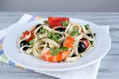 Fresh prawns with spaghetti, olives, tomatoes and parsley in a big round plate on a napkin on wooden