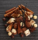 Different kinds of chocolates with spices on dark background