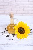 Sunflower with seeds and oil on table on brick wall background