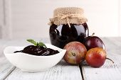 Plum jam and in glass dish, bowl of plum jam and fresh plums on wooden table on light background