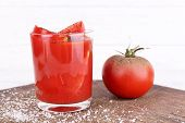 glass of tomato juice with spices and fresh tomatoes on wooden table