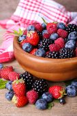 Ripe sweet different berries in bowl, on old wooden table
