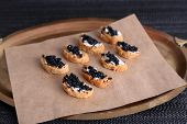Slices of bread with butter and black caviar on paper on tray on fabric background