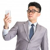 Asian business man with shocked facial expression while looking at smartphone, isolated on white bac