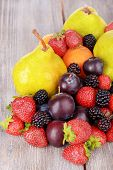 Ripe fruits and berries on wooden background