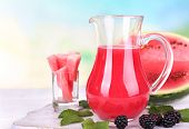 Watermelon cocktail in pitcher on wooden table on natural background