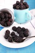 Sweet blackberries in mugs and on plate, on color wooden background