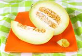 Melon on orange plate on  green tablecloth