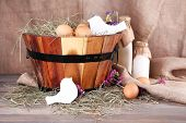 Big round basket with dried grass, milk and fresh eggs on sacking background