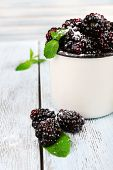 Metal mug of blackberries on wooden table on light background