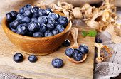 Wooden bowl of blueberries on cutting board on sacking napkin