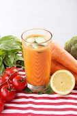 Glass of fresh carrot juice and vegetables on table cloth