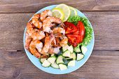 Plate of fresh boiled prawns with tomatoes, lettuce, lemon and avocado on a napkin on wooden backgro