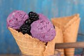 Tasty ice cream with berries in waffle cone on blue wooden background