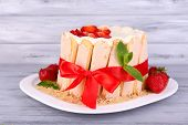 cake with fresh strawberries on wooden table