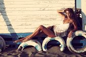 sensual young woman enjoy in sun sit on tires by the board wall wearing white top and bikini full body shot