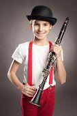 stock photo of clarinet  - little girl playing clarinet on a gray background - JPG