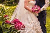 groom and bride stay together holding wedding bouquet
