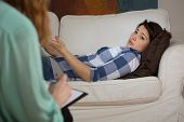 image of tell lies  - Depressed woman lying on the couch during psychotherapy session - JPG