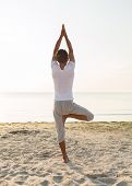 fitness, sport, people and lifestyle concept - man making yoga exercises on sand outdoors from back