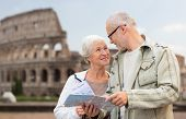 family, age, tourism, travel and people concept - senior couple with map and city guide on street over coliseum background