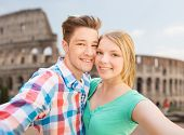 travel, tourism, technology, people and love concept - smiling couple with smartphone or camera taking selfie over coliseum background
