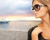 people, fashion, eyewear, travel and concept - beautiful woman in shades over sea with boat and sky background