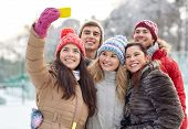 people, friendship, technology, winter and leisure concept - happy friends taking selfie with smartphone outdoors