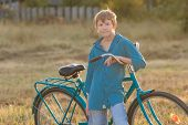 Portrait of teenager with blue bike in farm field