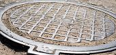 pic of manhole  - Metal manhole cover with checkered surface - JPG