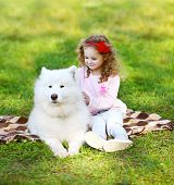 Child And Dog Resting On The Grass In Warm Sunny Day
