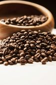 Closeup Of Blurred Wodden Bowl With Roasted Coffee Beans Over Black Background